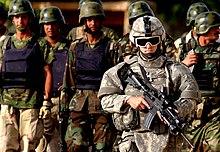 Konepistoolilla varustettu sotilas joukon univormusotilaiden edessä