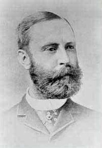 A black-and-white photographic portrait of a man with a thick beard and mustache wearing a high collar and jacket. It is faded around the edges.