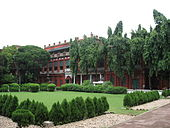 A brick-red mansion in the background, shaded by a row of large trees; in the foreground, a manicured lawn with a perimeter of trimmed round bushes.