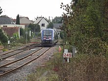 "View of a moving train with ""Loches"" on a sign"