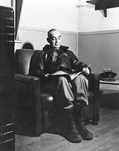 A man wearing a bomber jacket and ski boots sitting in an armchair, reading.