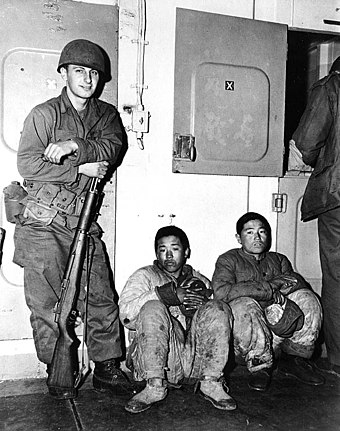 A US Marine guards North Korean prisoners of war aboard an American warship in 1951. KoreanWar NKPA POW.jpg