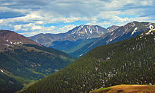 A view of mountainous terrain with a forested valley at the bottom rising to bare slopes with snowfields higher up. In the center one peak stands higher than the others.