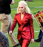 Lady Gaga in a red pant-suit walking on a field.