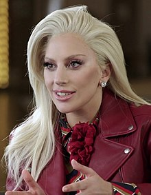 A picture of a smiling Lady Gaga, as she is looking away from the camera.