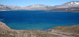 Laguna del Maule is a blue lake surrounded by barren and partially snow-covered mountains