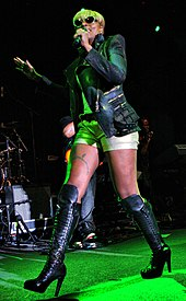 A woman walks while she sings. She wears sunglasses, a leather jacket and boots, and a gray blouse and short pants.