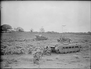 42nd Royal Tank Regiment - Troops of the King's Shropshire Light Infantry shelter behind a Matilda II tank of 42 RTR during manoeuvres at Knowsley Park, Prescot, 30 July 1940
