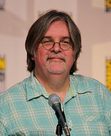 A man in glasses and a plaid shirt sits in front of a microphone.