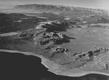 Chain of tall hills with sharp peaks. A crater and lake are in the foreground.