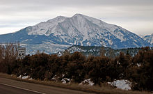 A snow-covered peak under a low overcast sky, seen from a road with bare brown vegetation in the foreground. To the left is a sign giving the speed limit as 65 miles per hour