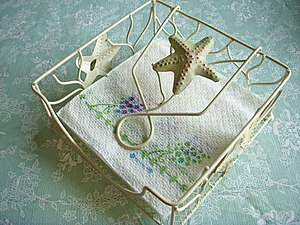 Napkin holder - A horizontal napkin holder with a weight to hold napkins down and edges
