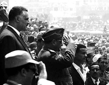Egyptian President Gamal Abdel Nasser (standing to the left) welcomed by Yemeni crowds on his visit to Sana'a, April 1964. In front of Nasser and giving a salute is Yemeni President al-Sallal. Nasser and Sallal in Sanaa.jpg