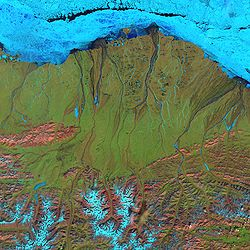 Landsat 7 false-color image of the North Slope. Along the coast, fast ice still clings to the shore in a solid, frozen sheet. At the top of the scene is the drifting sea ice. A dark blue strip of open water, known as a flaw lead, separates the fast ice from the drifting sea ice. The Brooks Range is visible at the bottom.