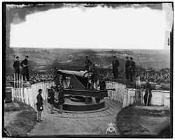 Historic photograph of a Union gun crew posed with a large cannon, behind earthwork fortifications and overlooking a large stretch of countryside