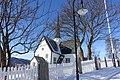 """Oppdal Church (kirke, kyrkje, """"Maret på Vang""""), Gauldal deanery (prosti), Oppdal municipality, Trøndelag county, Norway. Cruciform style 1651. Blue sky, snow, fence, graveyard, view, etc. 2019-03-19 lamp J.jpg"""