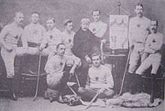 A group of men wearing their team uniforms, some standing and some sitting, each with a hockey stick, in a studio. On an easel is an Ottawa championship banner, on a table is a trophy.