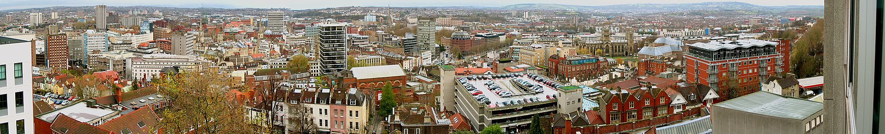 A panoramic view looking over a cityscape of office blocks, old buildings, church spires and a multi-story car park. In the distance are hills.