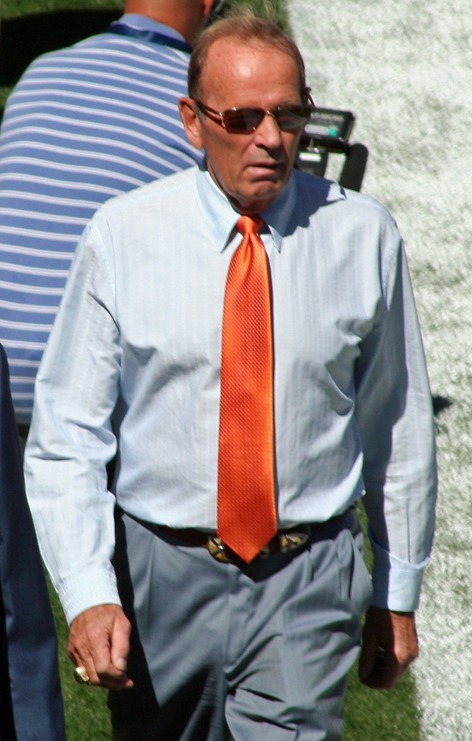 Candid photograph of Bowlen walking on a football sideline wearing blue-grey slacks, a light blue shirt with a red tie and sunglasses.