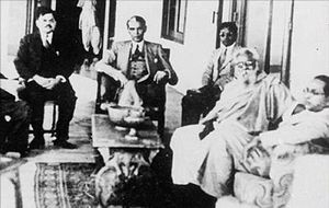 Five men sitting in chairs around a small table. Four of them are wearing suits and one is wearing a shawl and a dhoti. The one wearing the shawl has a flowing white beard.