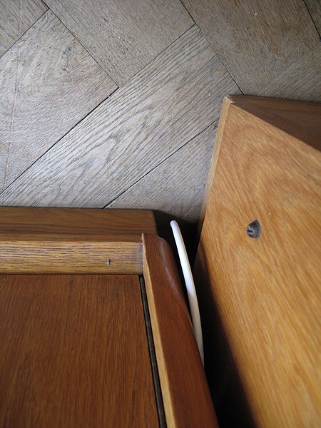 File:Pes zastrčený mezi skříně.JPG