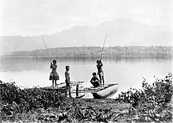 Black and white photograph of three men and a woman with a moored canoe.  Land can be seen in the background, across the water, with a forest and distant mountains.