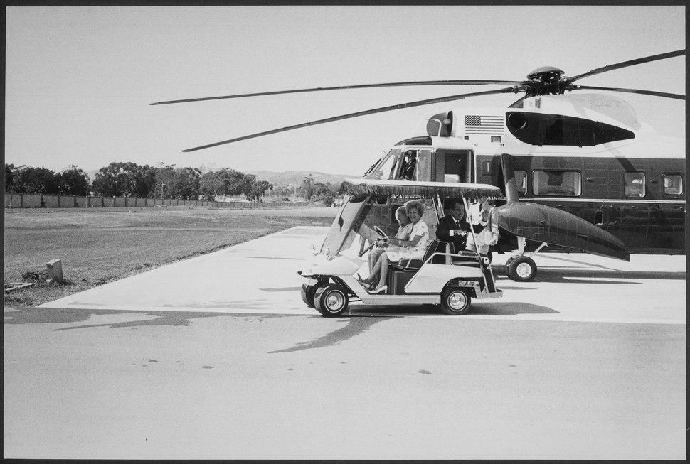 President and Mrs. Nixon and Tricia Nixon, on golf cart, approaching %22Marine One%22 - NARA - 194682