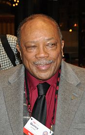 An elderly African-American man. The male is wearing a grey jacket open and a wine color shirt with a black tie.