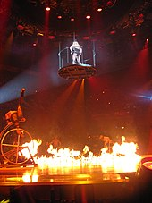 Image of a stage. In the center, a blond woman wearing a leotard and a black hat is in mid-air, standing inside a circular platform suspended by wires, the center of the stage is covered with fire. Several performers are in the sides of the stage, doing acrobatics in jungle gyms.
