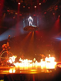 Image of a stage. In the center, a blond woman wearing a leotard and a black hat is in mid-air, standing inside a circular platform suspended by wires. The center of the stage is covered with fire. Several performers are in the sides of the stage, doing acrobatics in jungle gyms.