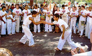 ' ' from the web at 'https://upload.wikimedia.org/wikipedia/commons/thumb/2/2c/Roda_de_capoeira1.jpg/390px-Roda_de_capoeira1.jpg'