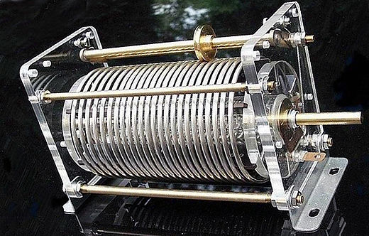 "A ""roller coil"", an adjustable air-core RF inductor used in the tuned circuits of radio transmitters. One of the contacts to the coil is made by the small grooved wheel, which rides on the wire. Turning the shaft rotates the coil, moving the contact wheel up or down the coil, allowing more or fewer turns of the coil into the circuit, to change the inductance. Rollspule.jpg"