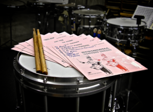 Mitch Markovich -  Rudimental Contest Series sheet music, perched atop a modern marching snare drum, with the cover featuring an illustration of Frank Arsenault