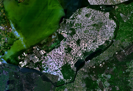 The Flevopolder in the Netherlands, reclaimed from the IJsselmeer, is the largest reclaimed artificial island in the world. Satellite image of Flevopolder, Netherlands (5.48E 52.43N).png