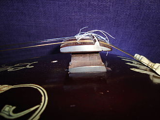 Jivari - Side view of a Tanjore-style rosewood tanpura bridge with cotton threads adjusted for full resonance.