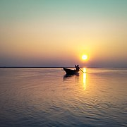 Silhouette of a fisherman on boat during sunset at Brahmaputra River, Assam, India.jpg