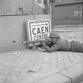 """A soldier lies prone, rife at the ready by a building in a city street. Beside him is a sign reading """"Caen centre"""", pointing back the way he has come."""