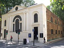 A large white building, dominated by a single large arched window. Another side of the building, faced in brick, recedes into the distance along a narrow street.