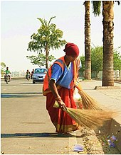 Woman sweeping the road