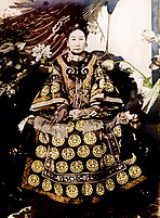 Full-face black-and-white photo of a woman with long fingernails sitting on a throne, wearing a richly adorned robe, a complicated hairdo, and a multi-layered pearl necklace. There are different kinds of flowers around her, as well as what appear to be peacock feathers.