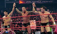 Three dark-haired men stand side by side in a wrestling ring with red ropes. The man in the center has tattoos on both his arms which are being raised in the air by the two men on either side of him. All three are wearing black wrestling tights.