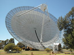 A big dish mounted on a short tower and open to the sky.