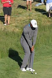 Le golfeur prépare son coup, mains jointes autour de son club au niveau de ses genoux.