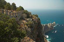 Сине-зеленое море окружает каменистый полуостров, покрытый зелеными деревьями и каменной стеной замка с crenelations.