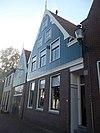 foto van Huis met houten van windveren in accoladevorm voorziene topgevel boven een pui van baksteen