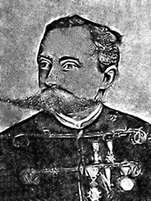 Sketch of the head and shoulders of a man with hair parted neatly to the side and an enormous moustache. He wears a dolman-style jacket and five medals.