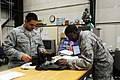 U.S. Air Force Airman 1st Class Kevin Jackson, right, an individual protective equipment (IPE) weapons journeyman with the 35th Logistics Readiness Squadron, issues a gas mask to Staff Sgt. Aaron Bradley 120209-F-VS478-001.jpg