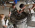 U.S. Air Force Airman Elizabeth Ulring, Airman Steven Power, an instructor, and Airman Brandinn Kim, all in the jet propulsion course with the 361st Training Squadron, ready a bearing housing on an F-15 Eagle 130827-F-NS900-002.jpg
