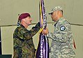 U.S. Army Maj. Jonathan Hartsock, right, the incoming commander for Joint Readiness Detachment-East, receives the unit flag from German Army Maj. Gen. Volker Halbauer, the Kosovo Forces commander, at a transfer 130526-A-ED406-409.jpg