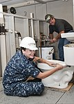 U.S. Navy Constructionman Jennifer Stewart, foreground, attaches a toilet tank to the bowl of a bathroom as Jeffery Brown tightens a dielectric union on a water heater at Sheppard Air Force Base, Texas, July 25 110725-F-NS900-013.jpg